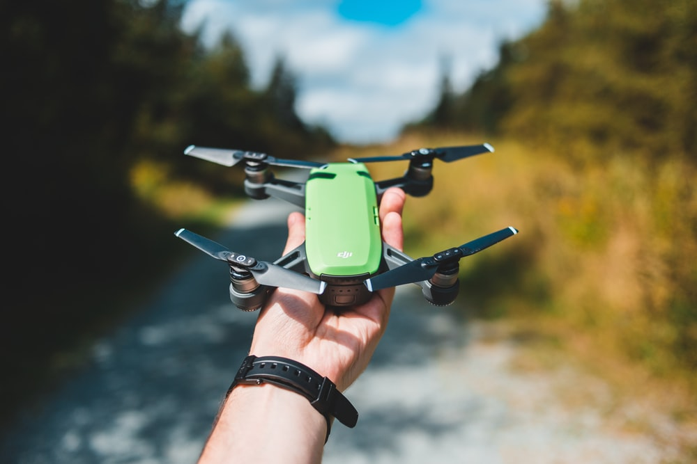 person holds green and black drone