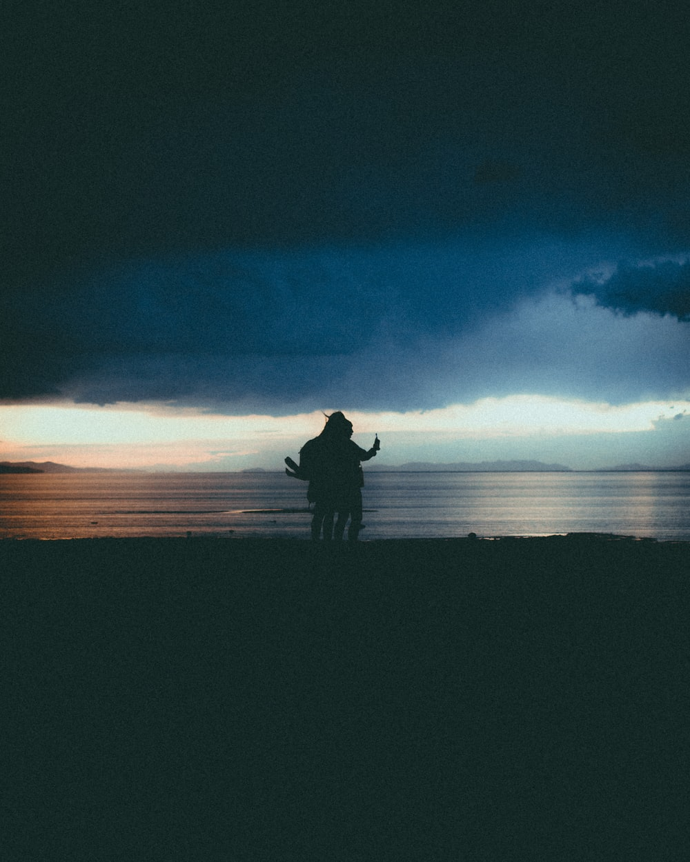 silhouette of man and woman standing on field during night time