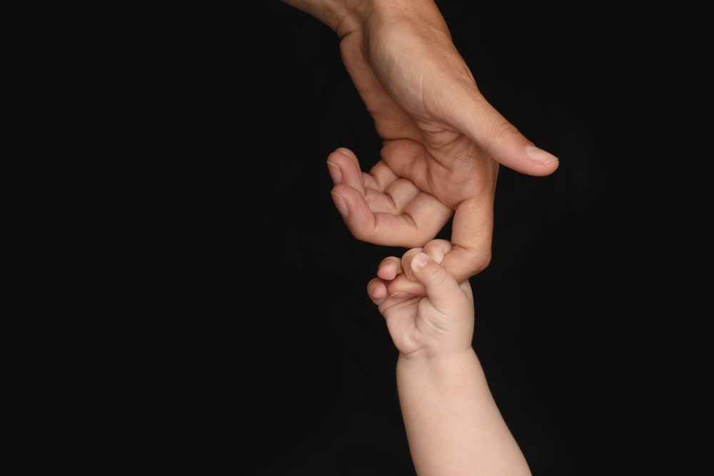 person and baby holding hands