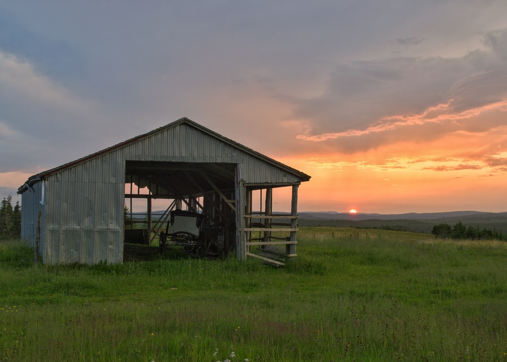 gray wooden house in green field under orange skies