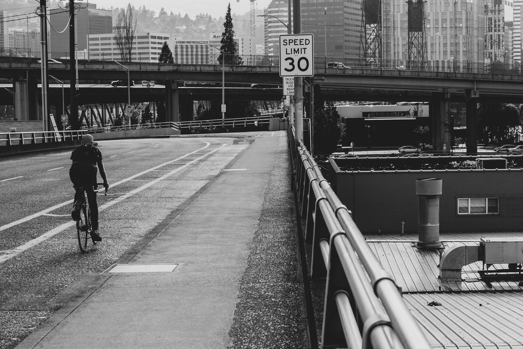 grayscale photography of person riding bicycle on bridge