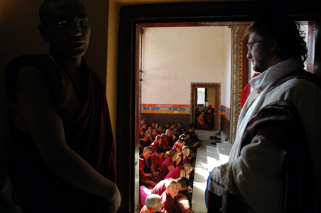 Monk to the left and a western Buddhist student wearing a full Tibetan chuba, adi, and katas, waiting for the master in the outer hallway, nuns seated, Tharlam Monastery, Boudha, Kathmandu, Nepal