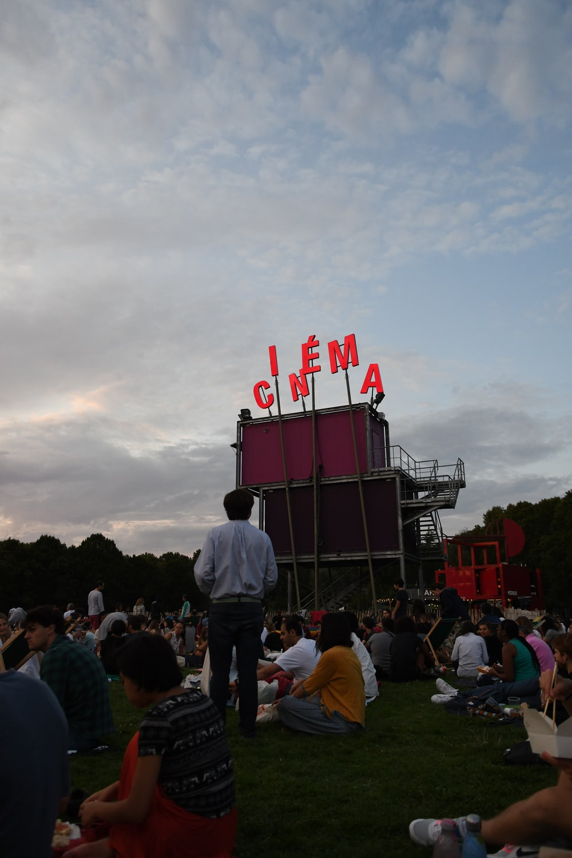 people sitting on field near cinema stage