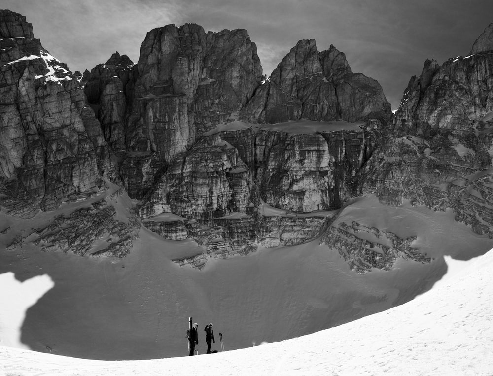 wide angle photography of two person standing beside mountain during daytime