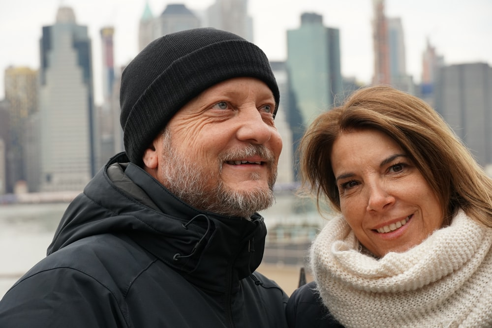 man and woman wearing coats standing near water