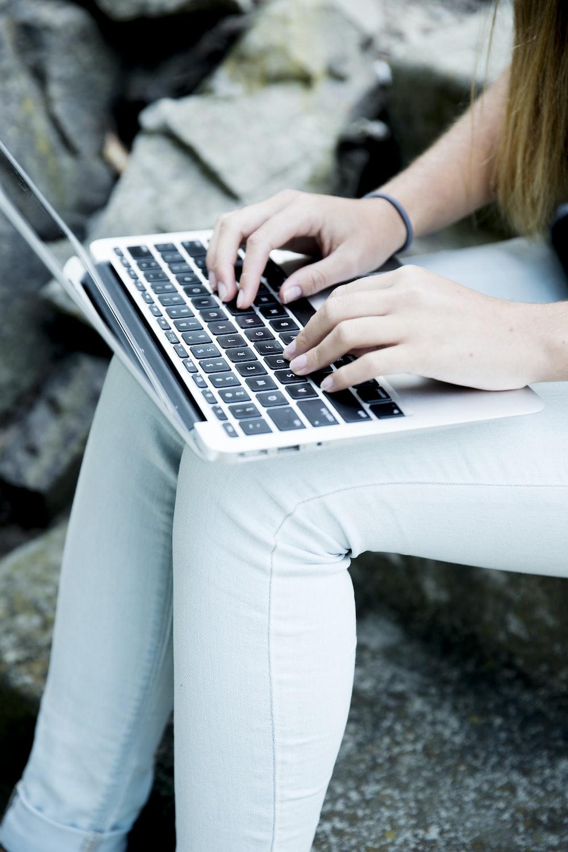 woman sitting on rock browsing laptop