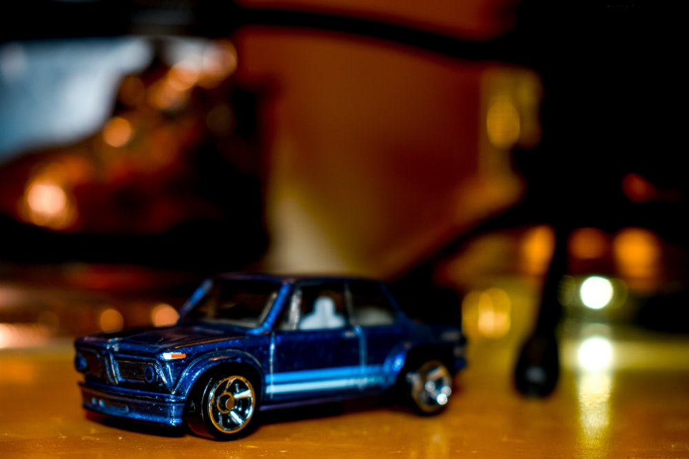 blue coupe toy on brown surface