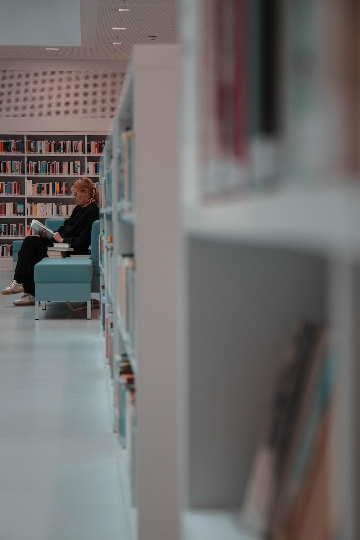 woman sitting beside bookshelves
