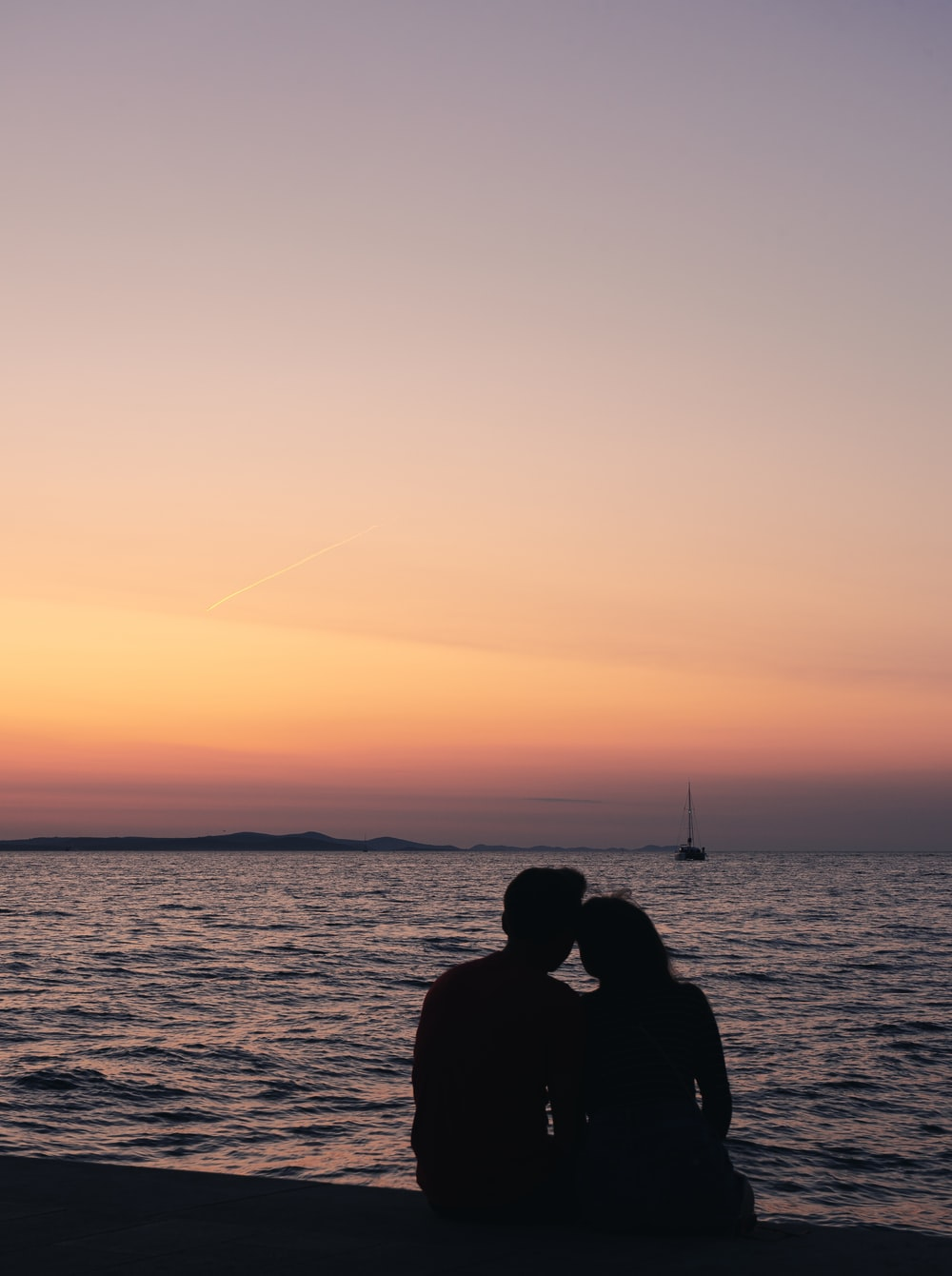 silhouette of man and woman sitting near body of water during sunset