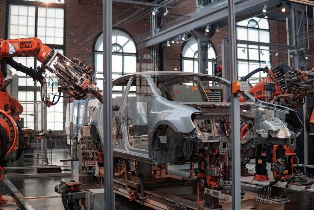 gray vehicle being fixed inside factory using robot machines