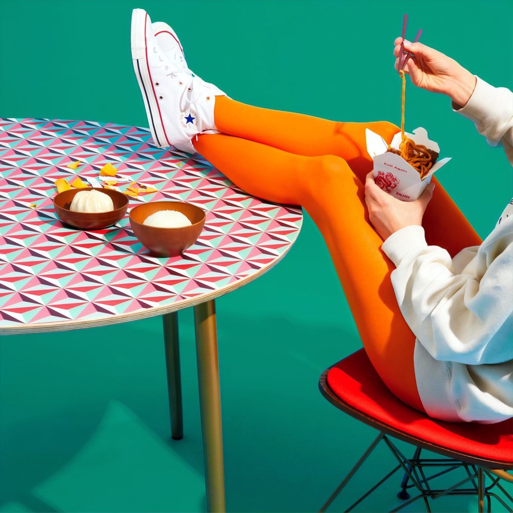 person siting while feet on table eating noodles