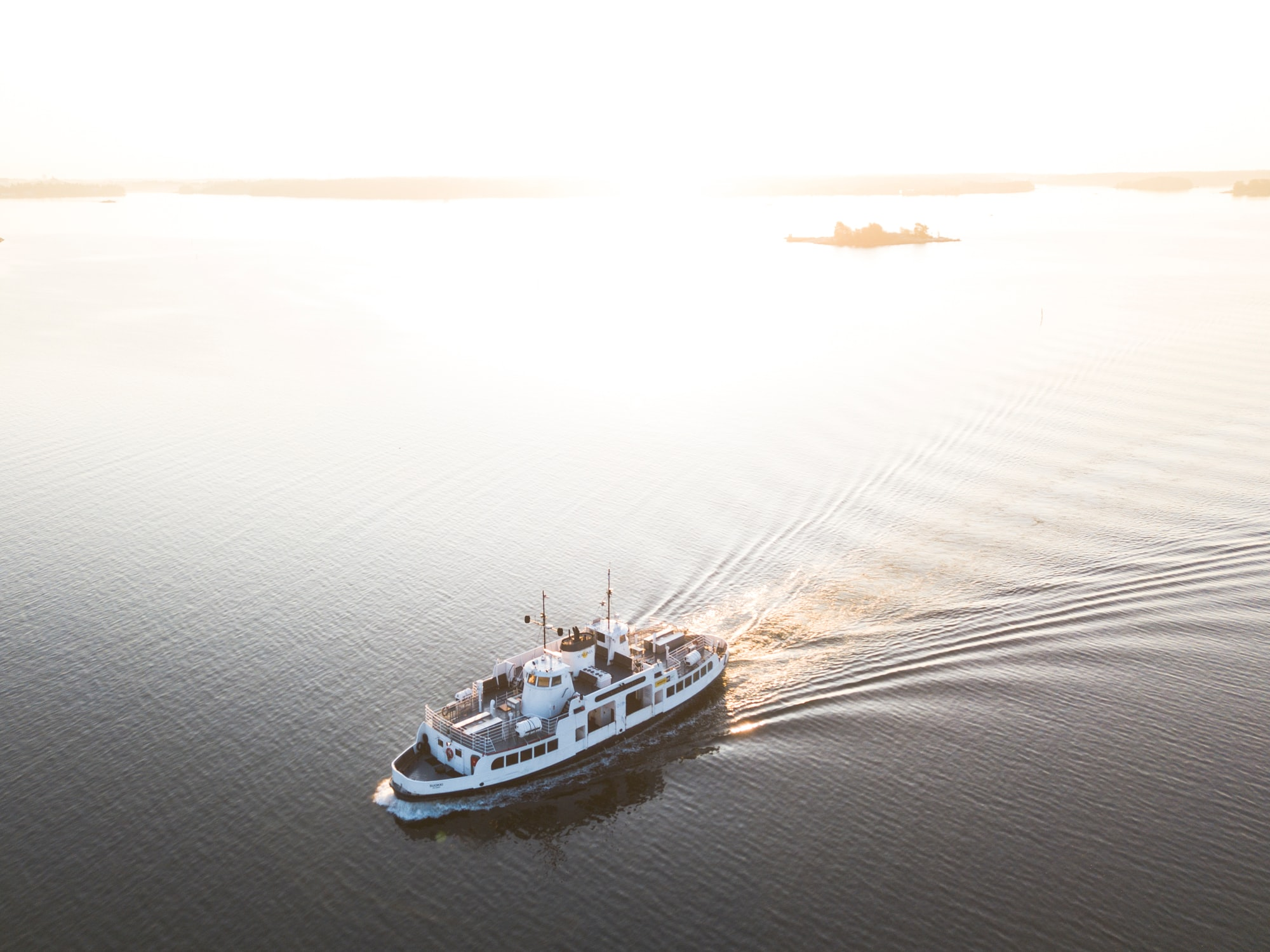 Top shot of a boat with two decks cutting through a water body.