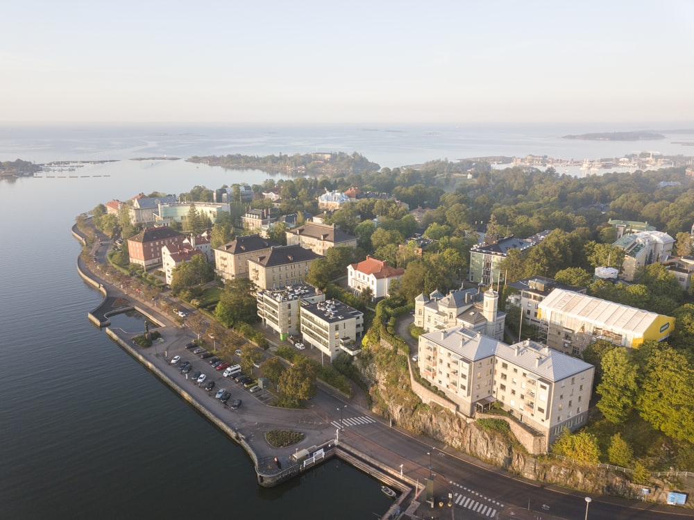 aerial photography of buildings surrounded by trees beside body of water
