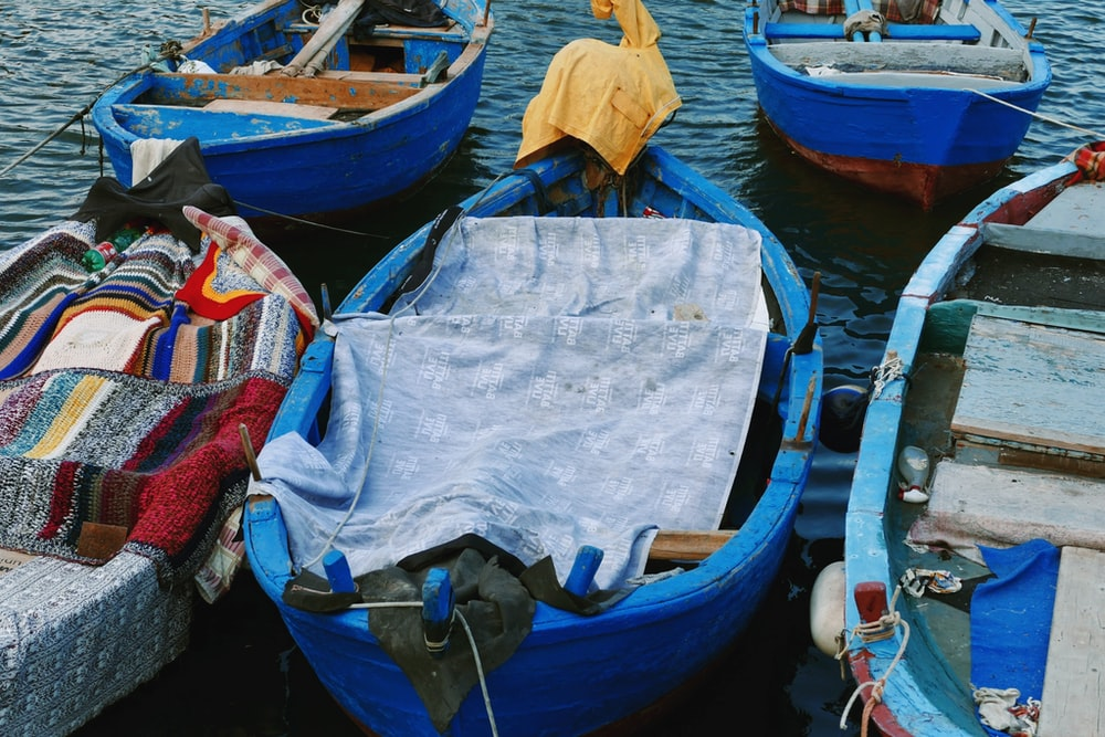 blue wooden boats on body of water
