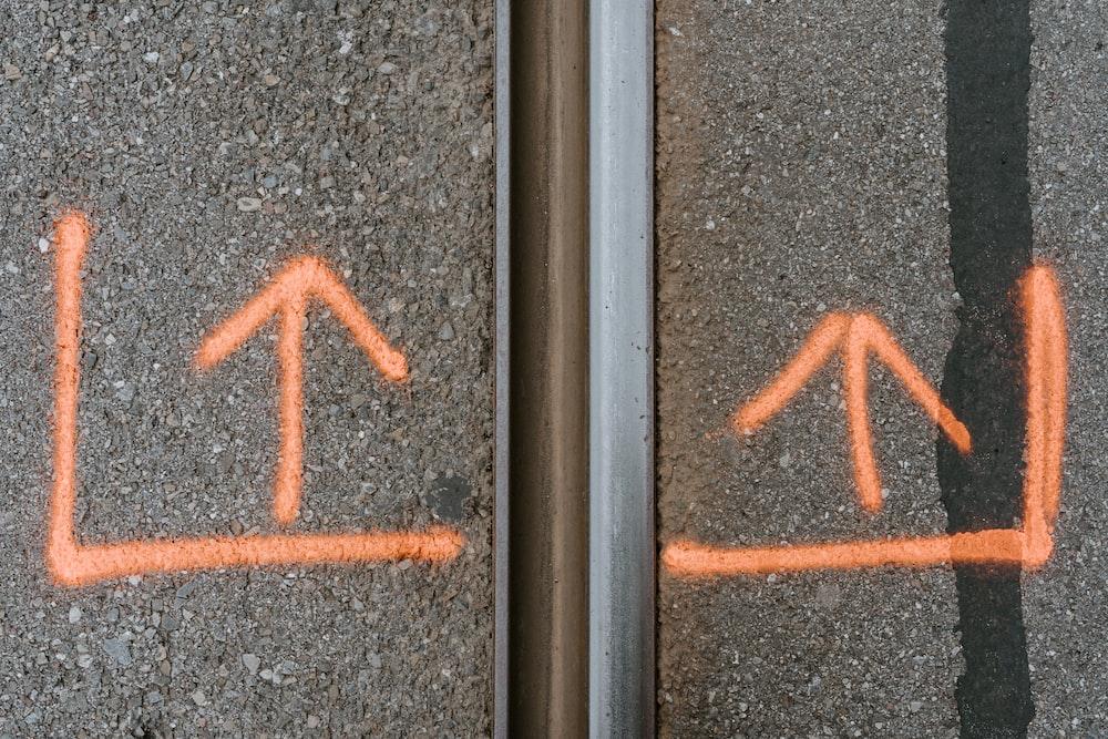gray concrete pavement with orange arrow