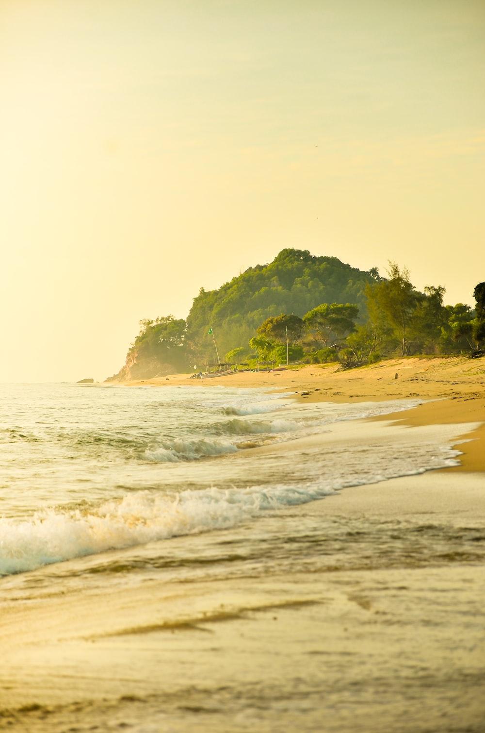 seashore viewing mountain during daytime
