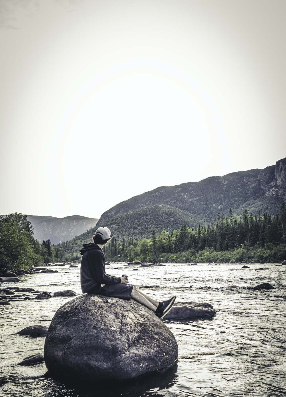 man sitting on rock viewing river and mountain during daytime