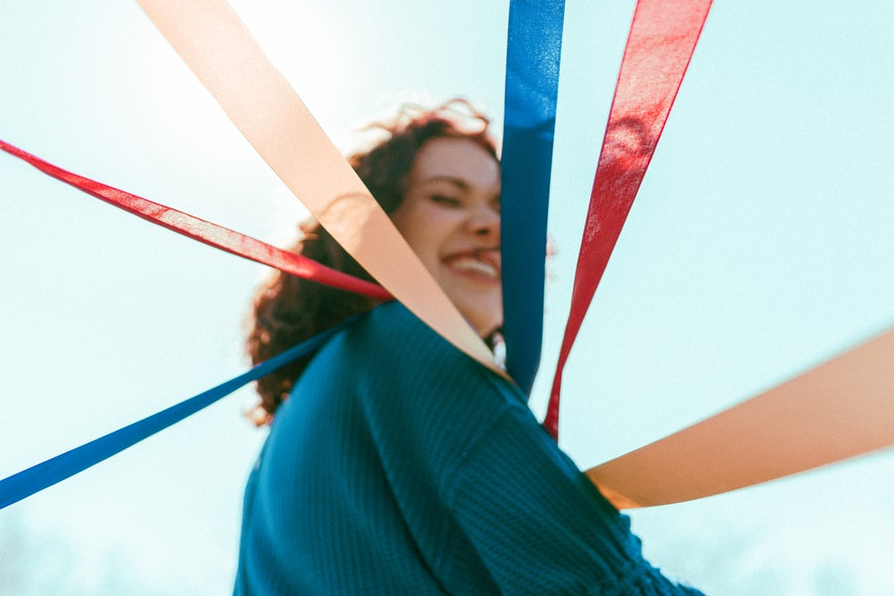 selective focus photography of smiling woman holding red, blue, and brown ribbons