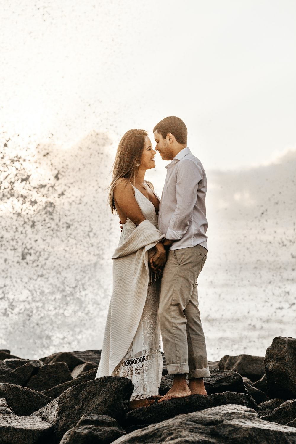 man and woman facing each other while standing on rock boulders in seashore
