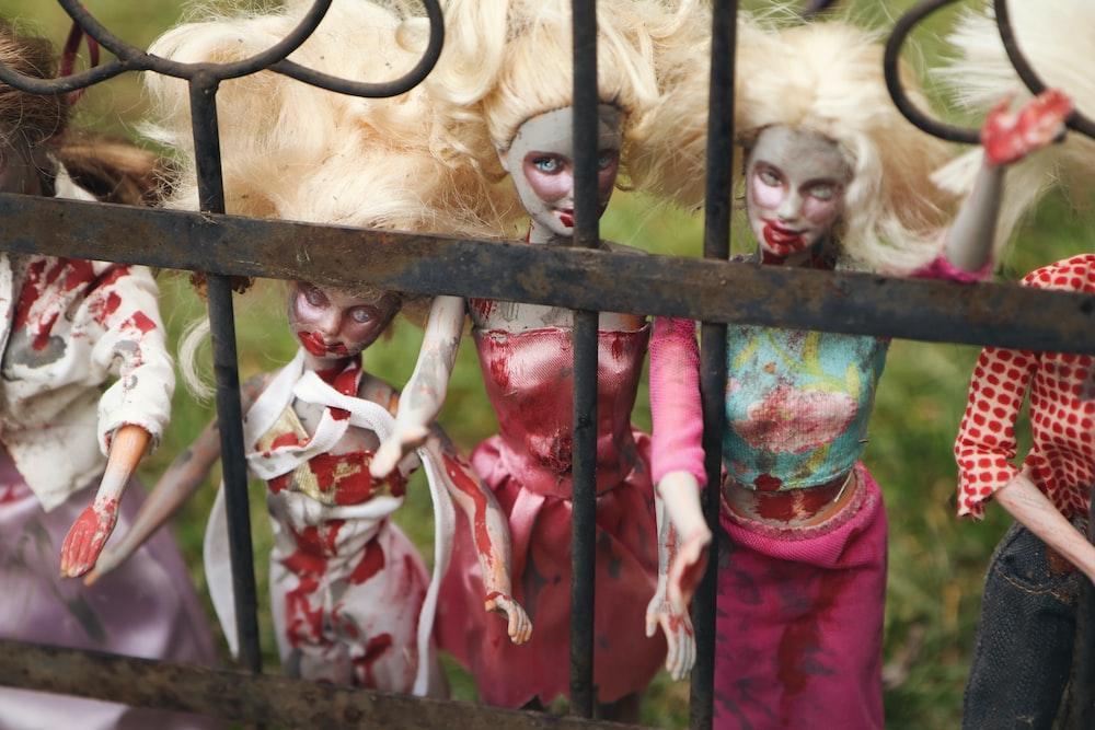 five zombie female dolls behind gate