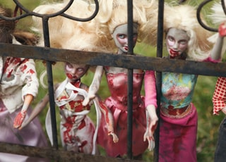 five zombie female dolls behind gate