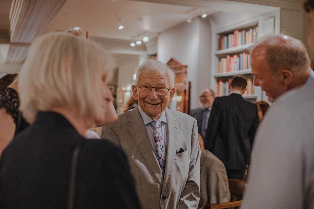 smiling man wearing suit standing beside man