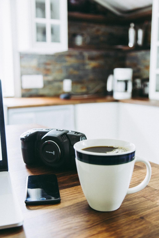 white and black ceramic mug beside DSLR camea
