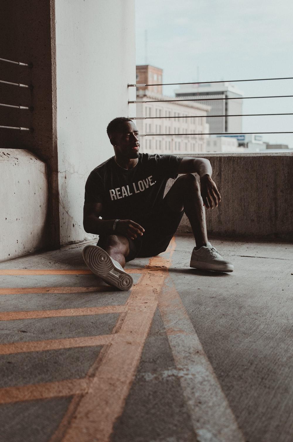 sitting man wearing Real Love shirt during daytime