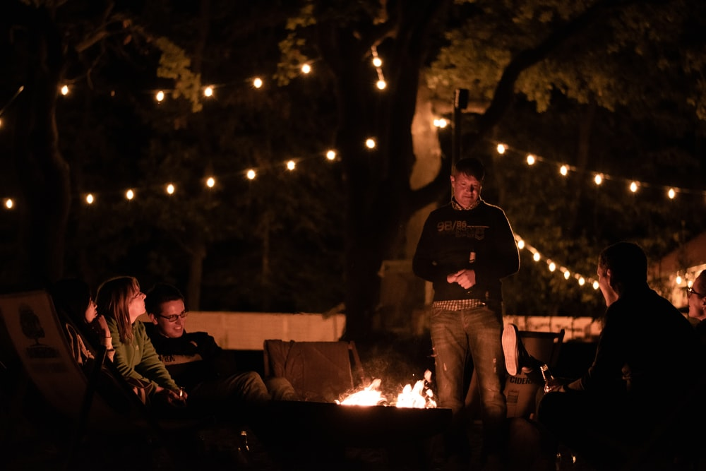 people standing and sitting around bonfire during night