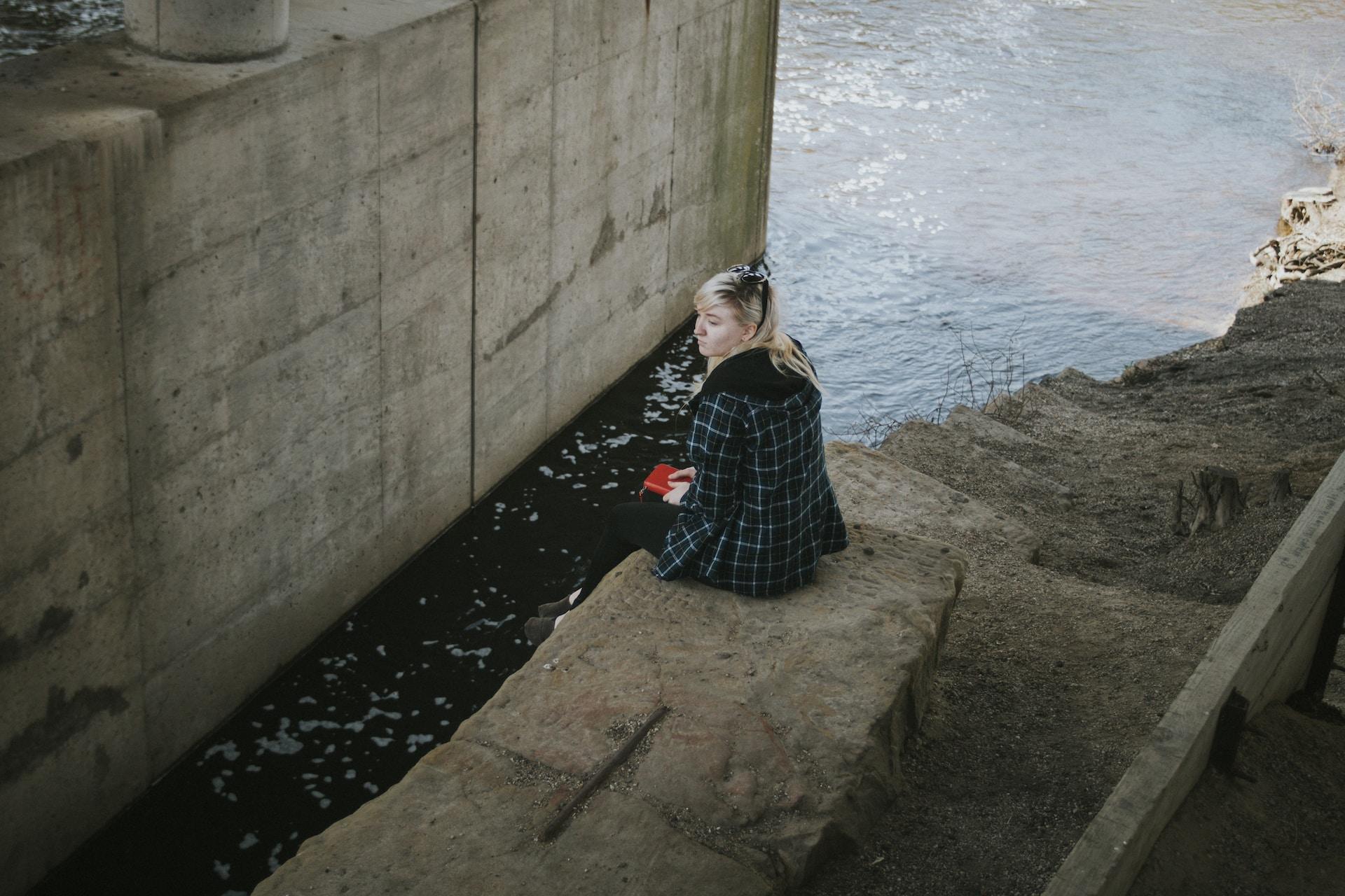 woman sitting beside river