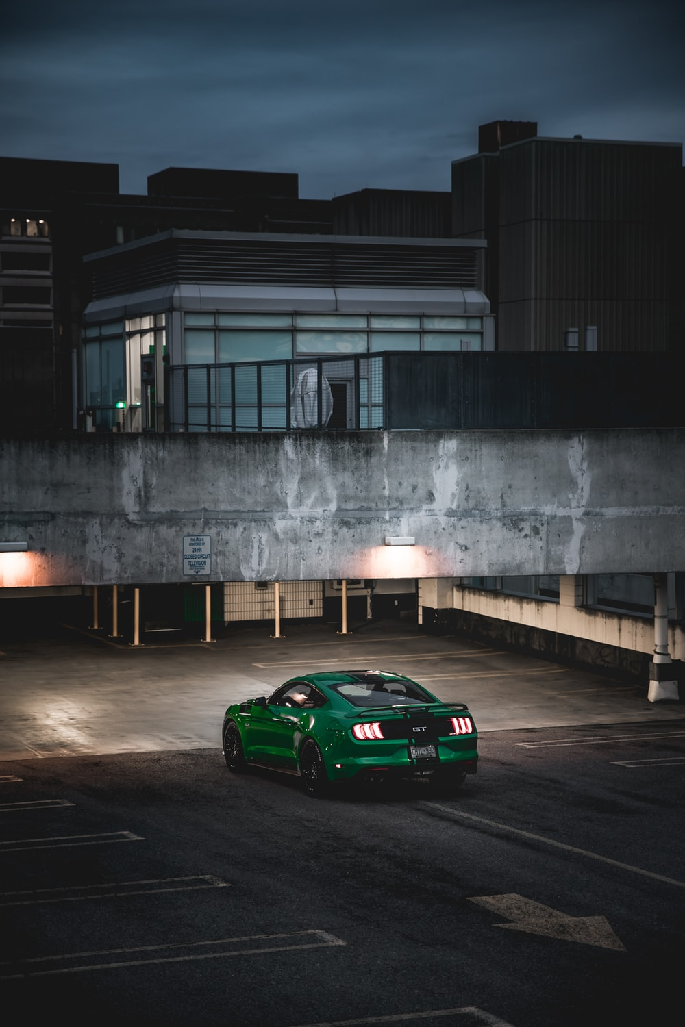 green coupe outside gray building