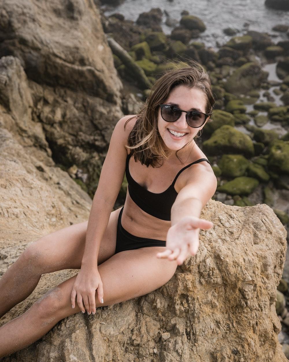 woman in black bikini sitting on rocky cliff