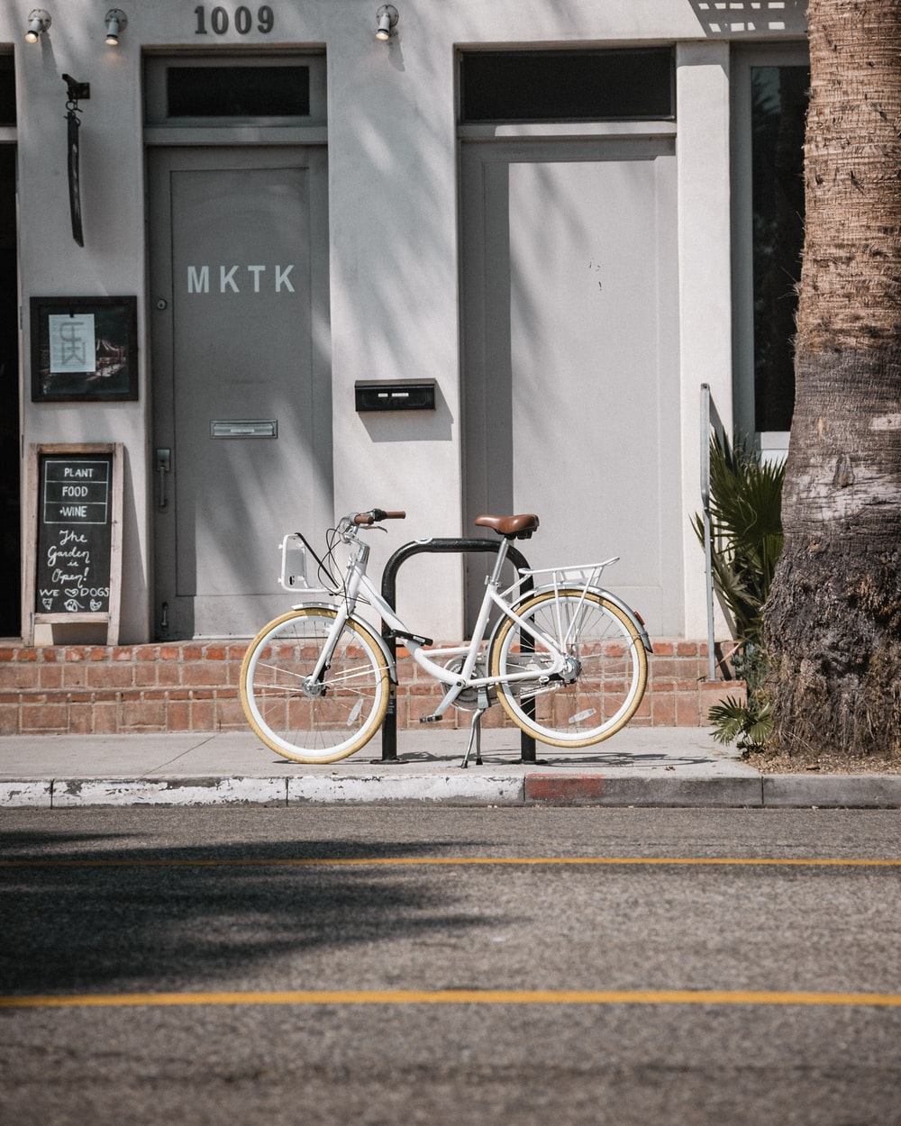 white commuter bike parks at paddock stand in front building number 1009
