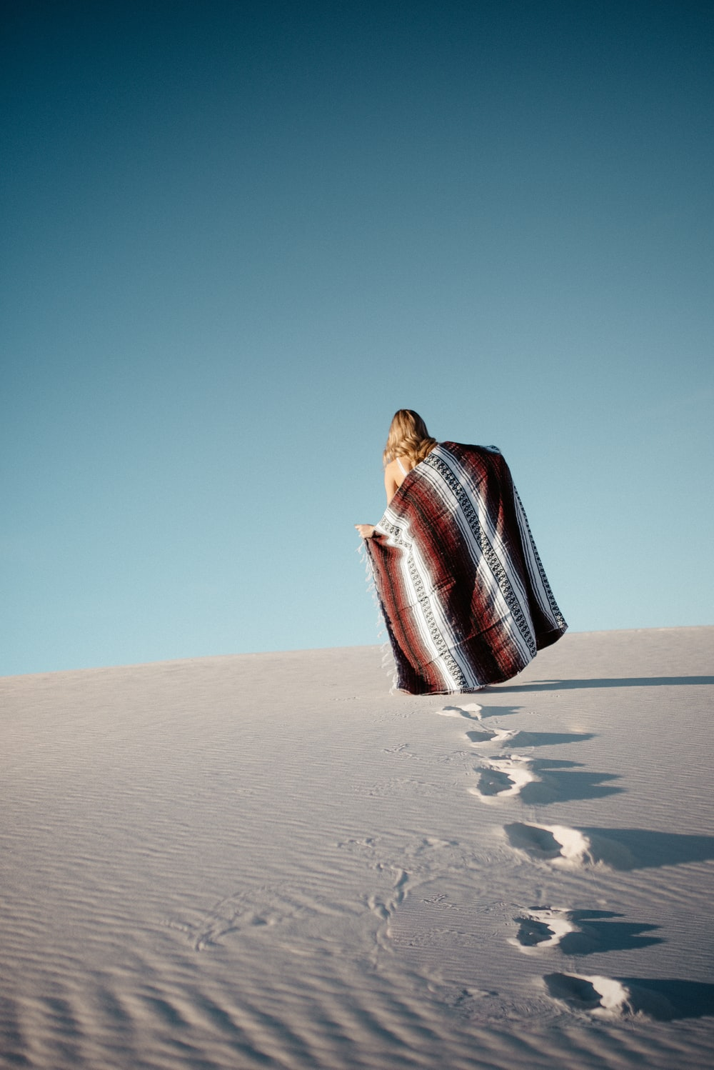 woman walks at the desert with scarf