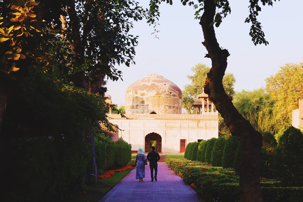 two person walking on pathway going on dome building during daytime