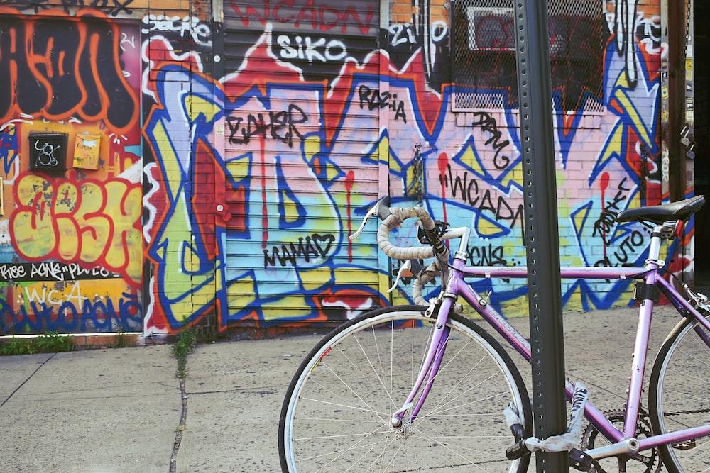 pink commuter bike near wall