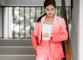 woman wearing pink and white ombre blazer and pants staring on her watch
