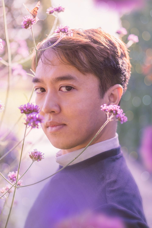 man near purple flowers