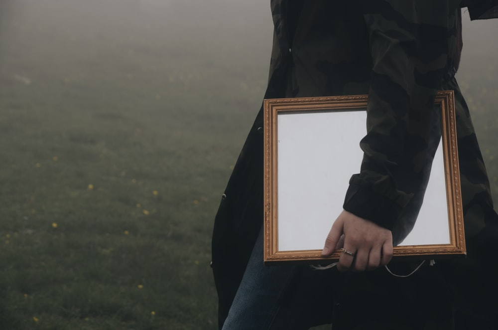 unknown person carrying rectangular mirror with brown frame