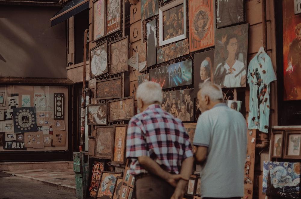two men walk inside art gallery