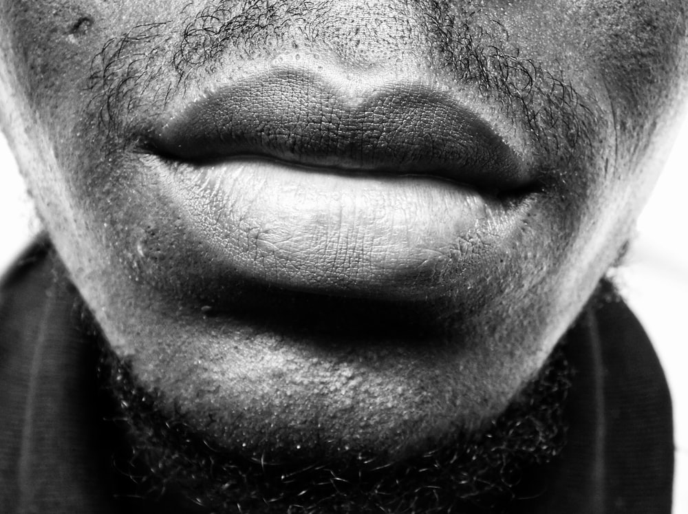 grayscale photo of man's lips and beard