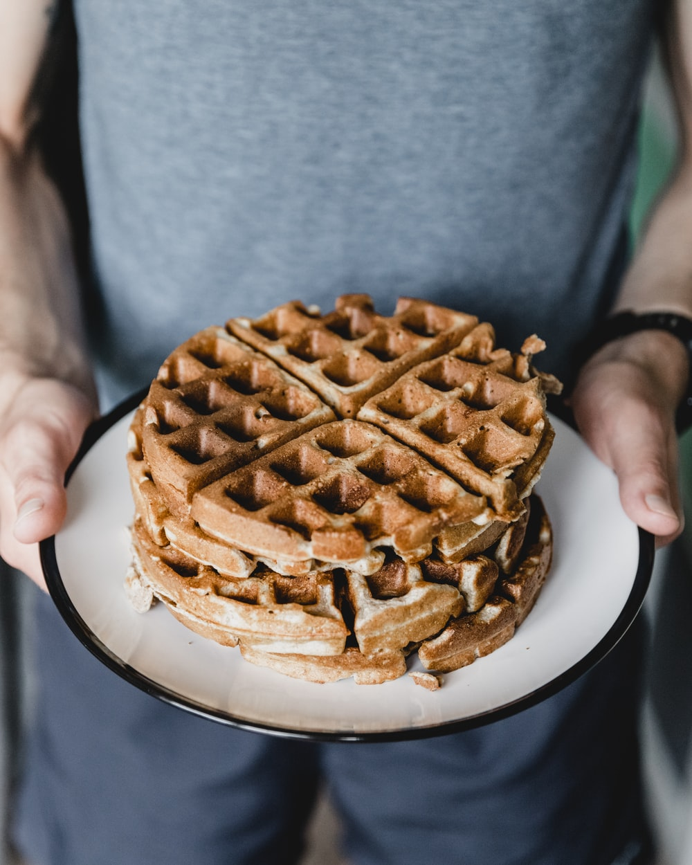 person holding plate with waffles