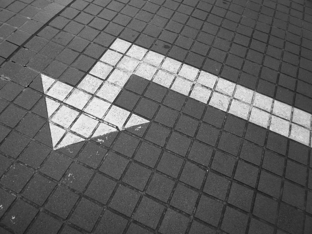 white arrow on bricked pavement