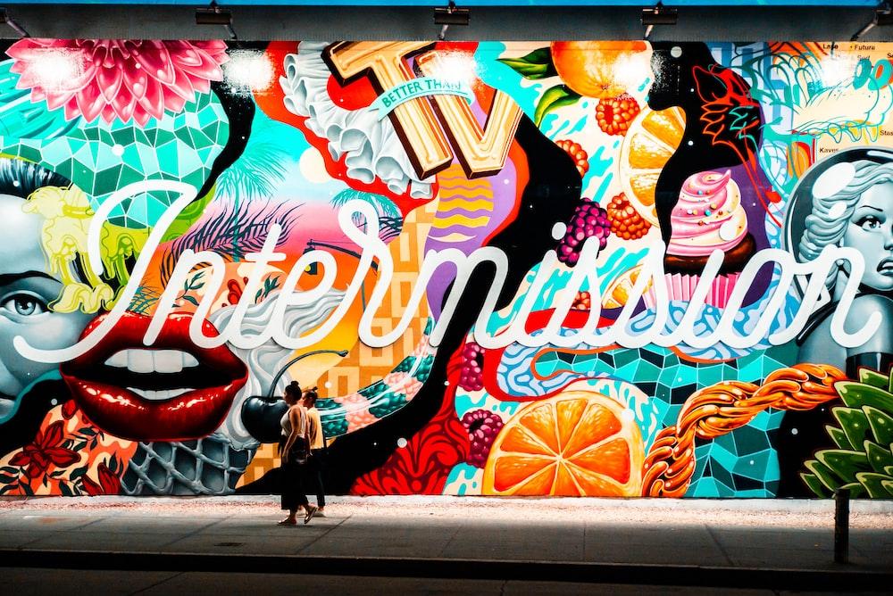 two women walking near multicolored graffiti art