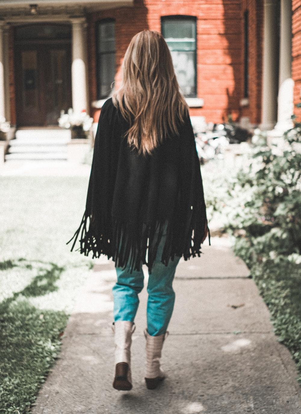 woman wearing black fringe cardigan walking on pathway