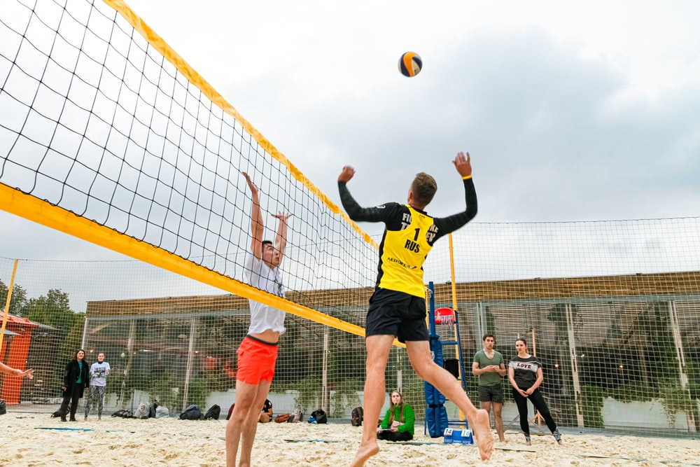 man wearing yellow and black long-sleeved shirt playing volleyball