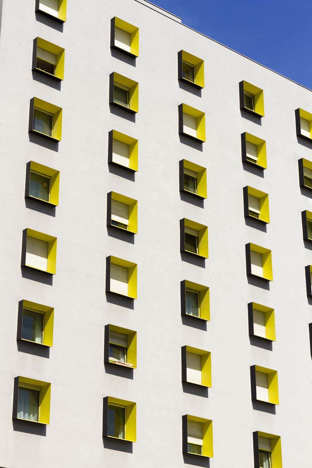 white building with yellow windows during day