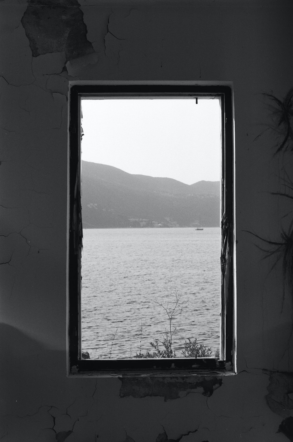grayscale photo of body of water through glass window