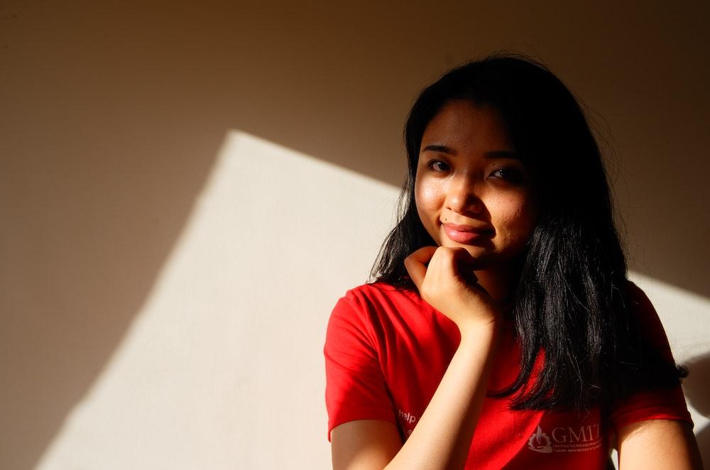 woman wearing red shirt sitting beside wall