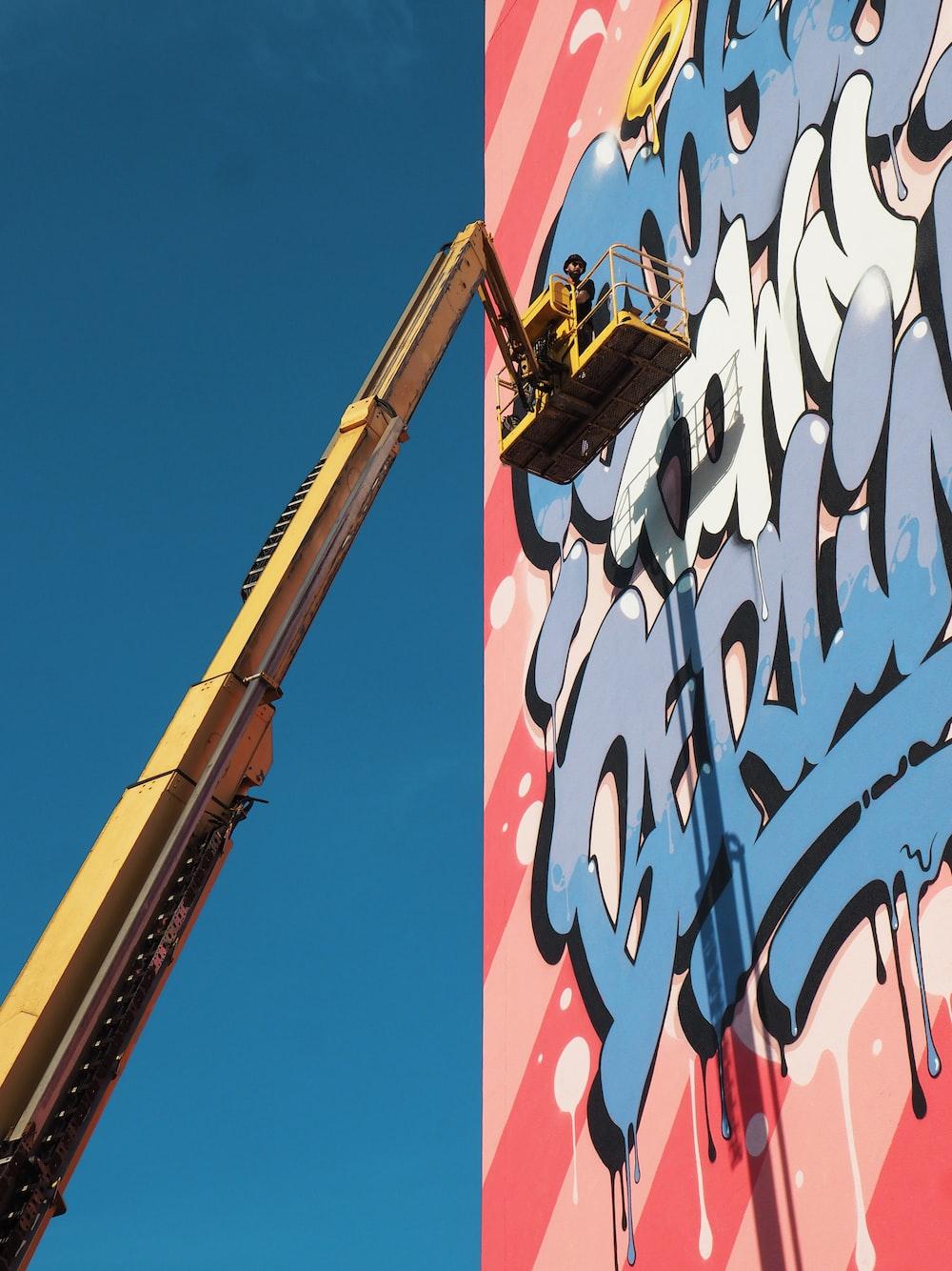 yellow bucket truck near graffiti wall art during daytime